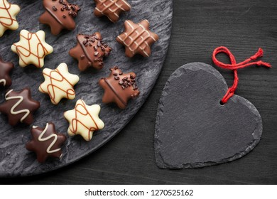 Star-shaped chocolates on dark grey stone board with black heart on dark textured background