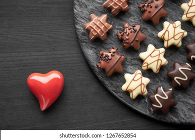 Star-shaped chocolates on dark textured background with red ceramic heart, Valentine or Christmas concept