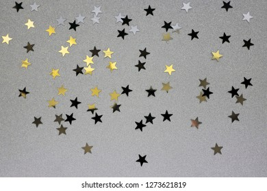 Star-shaped Confetti Sprinkled on a Silver Brocade Background. Black, Gold and Silver Glowing Stars. Funny Party Layout. Carnival Composition.