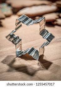 Star-shaped metal cookie cutter on wooden board