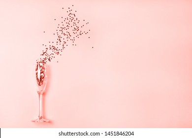 Star-shaped silver confetti poured out of champagne glass on pink background with copy space for text. Top view. Holiday and celebration concept.