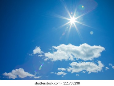 star-shaped sun in blue sky with light clouds