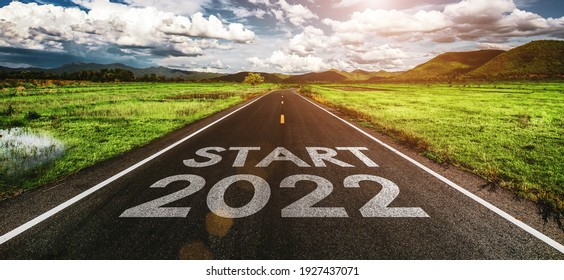 Start 2022 written on highway road in the middle of empty asphalt road and beautiful blue sky. Concept for vision new year 2022.