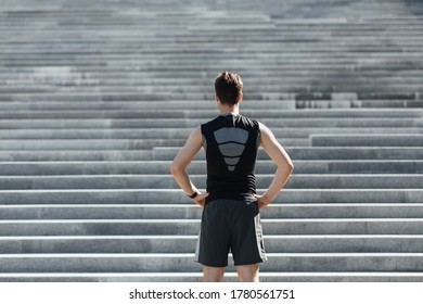 Start of ascent up. Muscular slender sportsman in sportswear looks at high stairs in city, free space