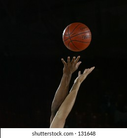 start of a basketball game with the jump ball as a white and black player go for the ball