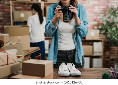 start up business woman hands holding professional camera shooting take photo of classic canvas casual shoes on wooden table with postal parcel selling online ideas concept. lady coworker in back.