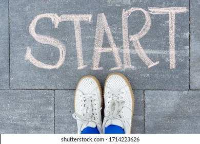 Start concept. Teenager girl standing legs on sidewalk in front of word hand written chalk start. Back to college