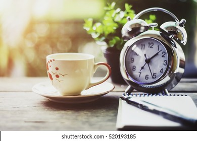Start up concept.Coffe cup,alarm clock,notebook.morning coffee day start,vintage tone.select focus cup.
