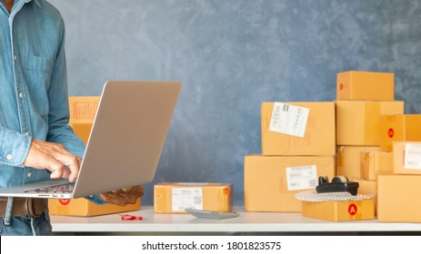 Start up entrepreneur of young asian man working with laptop computer and box for packaging order from shopping online in home for business online and online shopping.