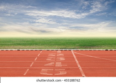 Start and Finish point of race track ,Running track number in front of tracks in stadium with beautiful green grass with blue sky scenery  background