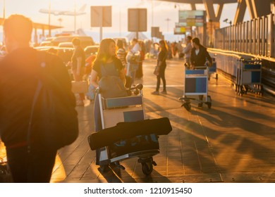 Start of her journey. Asian Woman carries luggage and trolley at the airport terminal during a wonderful sunrise and airplanes on background.