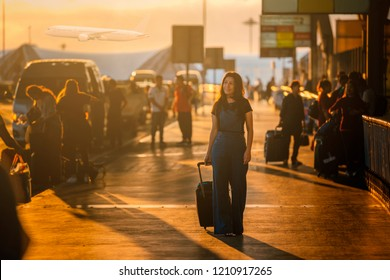 Start of her journey. Asian woman wearing casual clothes carries luggage at the airport terminal during beautiful sunrise and airplanes on background.