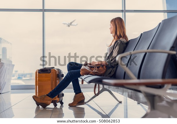 Start of her journey. Beautiful young woman looking out window at flying airplane while waiting boarding on aircraft in airport lounge