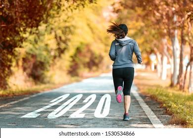 El comienzo del nuevo año 2020. Empezar a correr en la carrera de la naturaleza va a Objetivo de éxito.  Personas corriendo como parte del número 2020.  Concepto de deporte de vacaciones