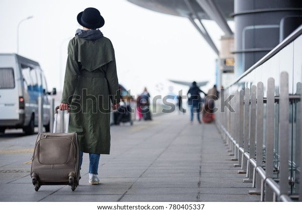 Start of journey. Full length of elegant lady in hat is carrying her suitcase while walking to the airport. Back view. Copy space in the right side