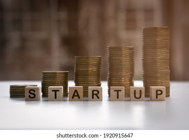 The start up letters on the wooden block cube and gold coin. Business ideas for starting a business. Business development concept.