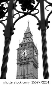 Start monochrome view of the famous clock tower of Big Ben framed by ornate Gothic wrought iron fencing surrounding Westminster Palace, London, UK