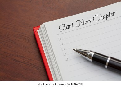 Start New Chapter words,Conceptual,notebook on a wooden table. open diary and pen to record