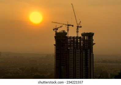 Start a new day dawning 0f the building under construction with crane and construction tools.