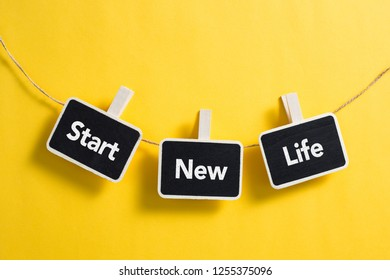 Start New Life concept small blackboard hanging on line.