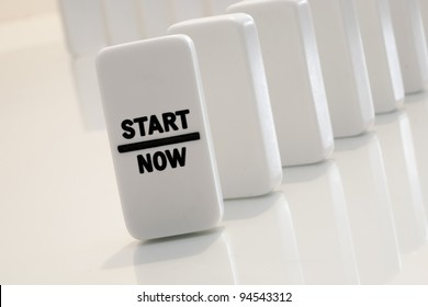 Start now message on aligned and standing dominoes