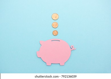 Start saving money early - 3 coins flying into a pink piggy bank on light blue background