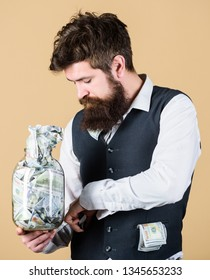 Start saving for your retirement as early as possible. Establish your budget. Businessman with his dollar savings. Security and cash money savings. Man bearded guy hold jar full of cash savings.