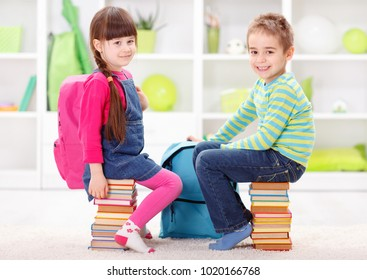 Start of school and learning - little pupils sitting on piles of books