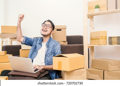 Start up small business entrepreneur SME or freelance asian man typing computer with box, Young success Asian man with his hand lift up , online marketing packaging box and delivery, SME concept