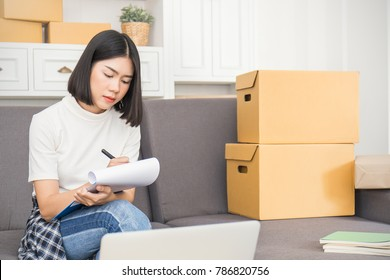 Start up small business entrepreneur SME, asian woman writing on clipboard. Portrait of young Asian small business owner girl at home office, online marketing packaging and delivery, SME concept