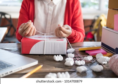 start up small business owner packing cardboard box at workplace. woman entrepreneur seller prepare parcel box of product for deliver to customer. Online selling, e-commerce, shipping concept