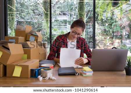start up small business owner working at workplace. freelance woman seller check product order to prepare for delivery to customer.  Online selling, e-commerce, shipping concept