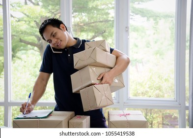 Start up. young man happy after new order from customer with clip board, mobile phone and delivery parcel box on table, small business owner working at home office, SME, shopping online concept