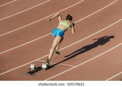 start women athletes from starting blocks in stadium