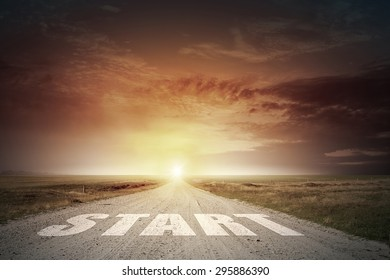 Start word on asphalt road and sunrise at horison line