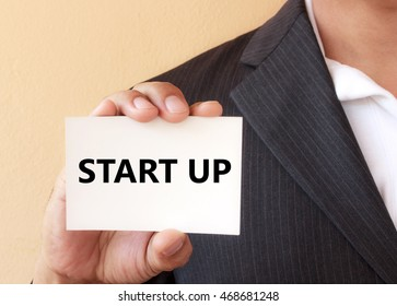 START UP word on the white card presenting by a businessman