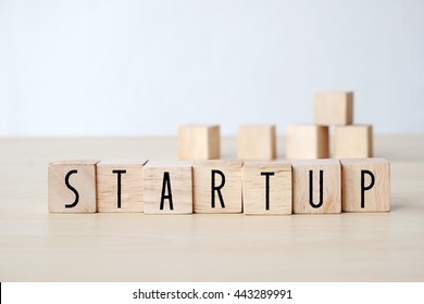 Start up word on wooden cubes background, business concept