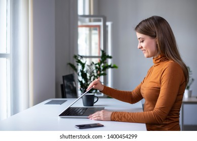 Start of a work day. Young woman opening laptop, getting ready for work in the morning at the desk near windows in a  beautiful office. Side view.
