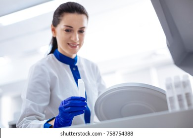 Start working. Selective focus of white medical container hold by brunette  enthuasiastic female laboratory assistant who wearing labcoat and smiling