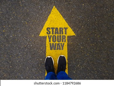 Start Your Way  text on yellow arrow on asphalt ground, feet and shoes on floor, personal perspective footsie concept