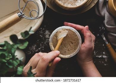 Starter sourdough. Female hands holding a jar with sourdough over wooden background.