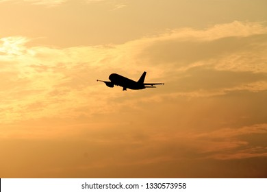 Starting airplane in front of the evening sun