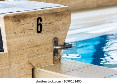 A starting block inside an empty and silent Olympic pool.