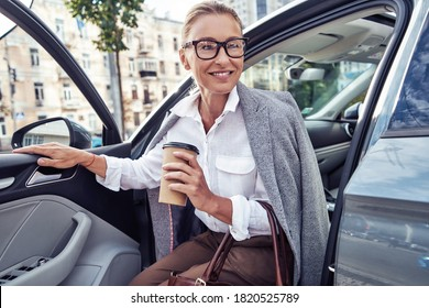 Starting day with coffee. Beautiful middle aged business woman arrived at work, she is getting out of her modern car and smiling