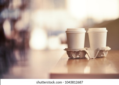 Starting day with coffee. two paper cups of latte on creamy blurred background.
