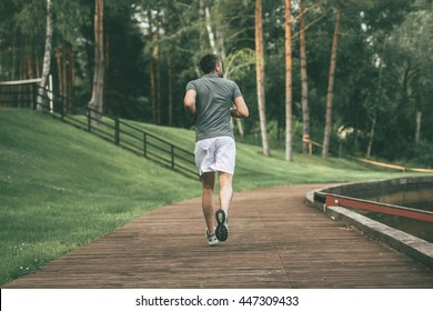 Starting day from morning jog. Full length rear view of young man in sports clothing jogging in park