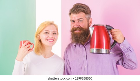 Starting day together. Modern technology make life easier. Couple prepare morning drink electric kettle. Electric kettle boils water quickly. Prepare drink in minutes. Save time modern technology.