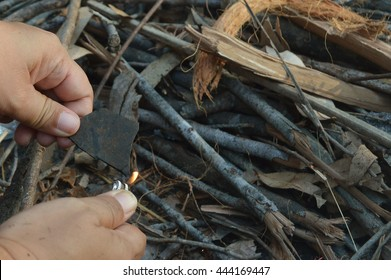 Starting a fire on firewood using a match and a piece of rubber. Starting a fire with basic items is one of life essential skill.