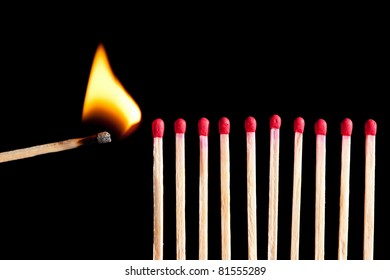 starting the fire - wooden matches in a row ready to burn, isolated on black background