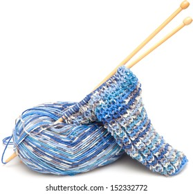 starting to knit - yarn, needles and beginning of a scarf isolated on white background